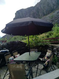Compact rear patio garden: table, chairs, umbrella, Weber BBQ & direct access to the mountain behind