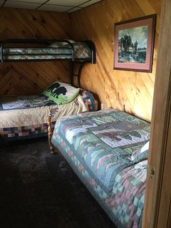 Second bedroom with a twin and double bunk bed and a separate twin bed.