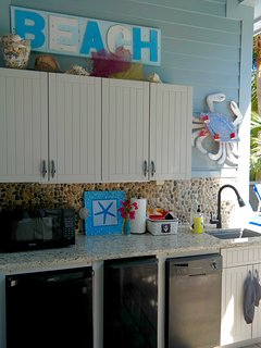 Poolside kitchen with refrigerator, ice maker, dishwasher, microwave and grill.