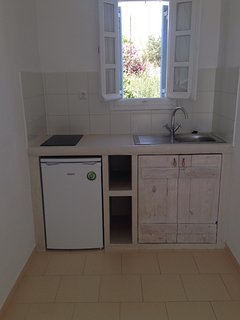 Kitchenette with mini-fridge/freezer, stove, and cookware, dishware and cutlery.