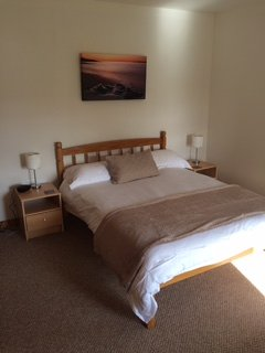 Master bedroom. New bed. Generous cupboard / storage space. New dressing & bedside tables. Clock.