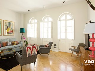 Living room with 3 large windows. Furnishes include a sofa and 2 armchairs.