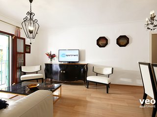 Living room furnished with sofa, 2 armchairs, coffee table and TV.