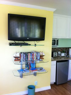Flat screen TV with cable channels, DVD player, assorted DVDs, and travel books.