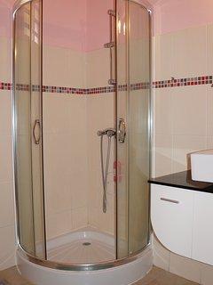 Salle de bain avec lavabo, douche et WC.