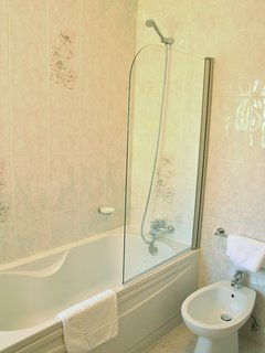 family bathroom with bath & shower toilet, bidet and sink.