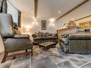 The main seating area's 4 piece leather Chesterfield suite includes a wing chair and sofa bed.