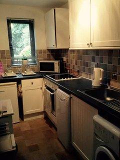 Kitchen: Electric cooker/hob, dishwasher, washing machine, fridge, microwave, toaster, iron/board
