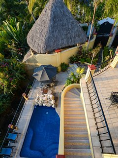 Looking at gardens from Palapa with pool side seating and outdoor shower.