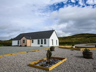 Cuillin Cottage with surrounding private garden, with open fields around.