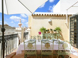 The terrace features a dining table, chairs, parasol and deck chairs.