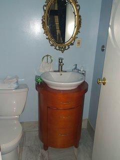 Half bathroom with sink and toilet. Marble floor.