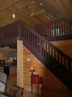 living room stairs to large loft with game area 2 twin beds and two sofa chair sleepers