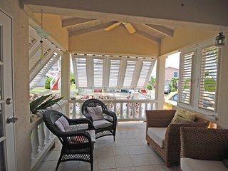 Outside sitting area by day, with shutters and overhead ceiling fan.