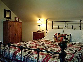 Master bedroom with comfy queen bed and newly installed fine antique dresser and nightstands.