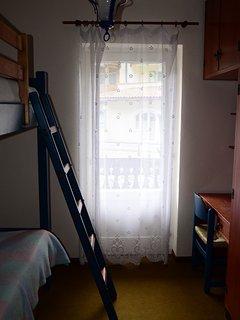 Camera (vista 1) con letto a castello, scrivania e armadio.