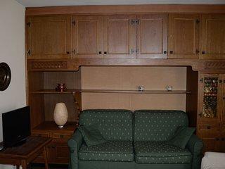 Soggiorno lato relax con divano-letto a 3 posti, poltrona e tv.