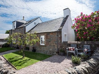 The pretty front garden is a great place to relax and enjoy views of the Eildon Hills