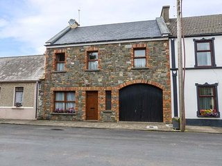 CARRIGAHOLT COTTAGE, open fire, mid-terrace, garden, pet-friendly, WiFi, in Carr