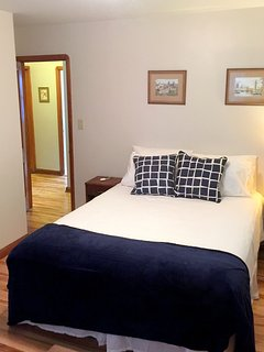 Guestroom 1 with Queen Bed two dressers, mirror, closet & linen closet.