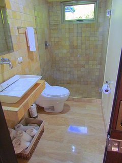 Travertine Floor modern bathrooms with on demand hot water.  4 Bathrooms.