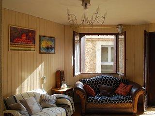 Salle de séjour avec deux canapés, télé HD et balcon