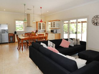Large family room including dining area and kitchen with adjacent fully equipped laundry