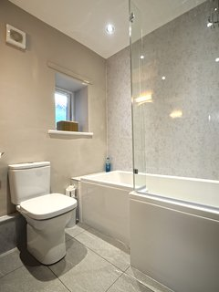 The modern bathroom has a bath with shower over, WC and pedestal basin with shaving light.