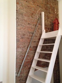 To the mezzanine.  The exposed chimney breast gives a glimpse of the apartment's Victorian roots.