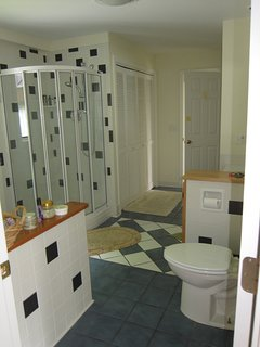 1st floor bathroom with full bath and enclosed shower, with washer and dryer tucked in closet.