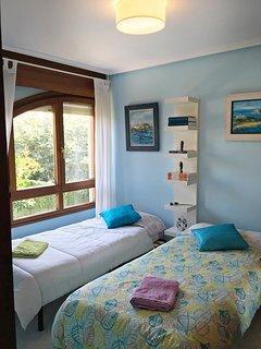 Habitación con dos camas individuales y con un espacioso armario ropero.