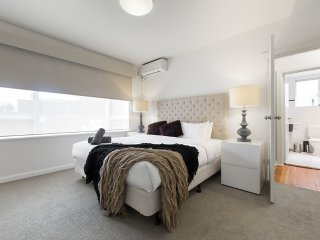 Spacious king bedroom with bedside tables, lamps, large mirrored robes, aircon & block-out blinds