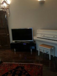 The flat screen tv in the lounge and up right piano.