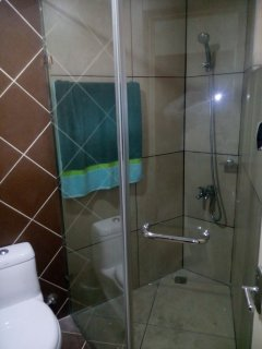 Bath with shower enclosure and rain shower
