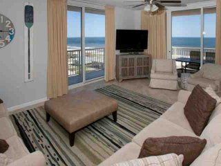 Living room with 55-inch TV and DVD player. Two sliding glass doors to Gulf-front patio.