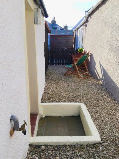 Back door with step up into gravelled area.
