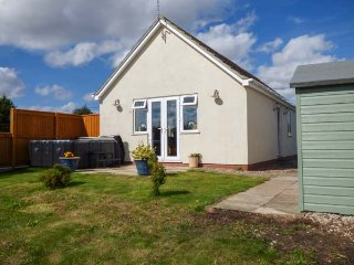 HAWTHORN COTTAGE, bungalow with hot tub, woodburning stove and off road parking,