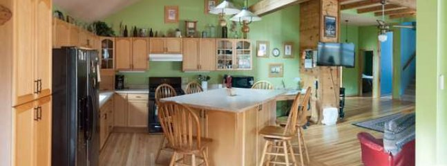 he enormous kitchen features a large island with lots of counter space for cooking and entertaining
