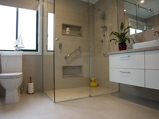 Hotel-style double walk -in shower, toilet and large vanity