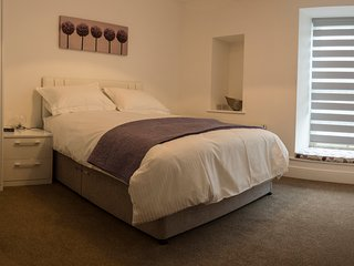 Bedroom with kingsize bed and fully fitted luxury wardrobes.