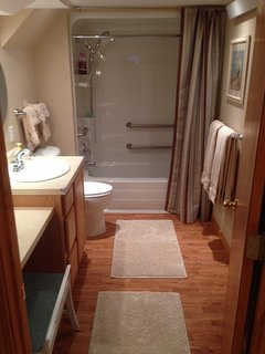 Full tub/shower with ADA grab bars, sit down vanity area next to sink. full rack of towels