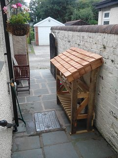 Log store outside the back door, made from spare materials with a cedar shingle roof