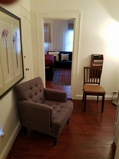 spacious foyer,  with a full size refrigerator, table and chairs and kitchen.