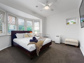 Accommodation Rosanna - Elegant queen bedroom with wall-mounted large TV & gorgeous old bay window