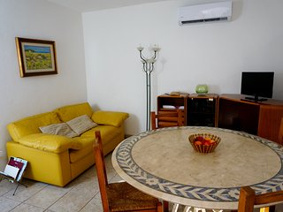 Living room with a big table, tv, a comfortable sofa and air con.