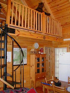 Spiral stairs lead to the sleeping loft area with twin beds