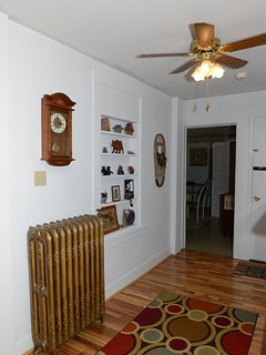 foyer leading to living room with antique gold radiator, ceiling fan