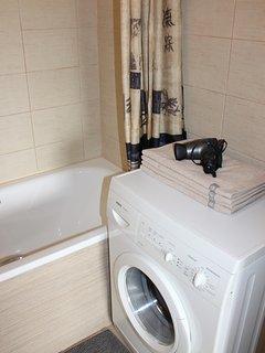 Bathroom with washing machine,  towels,  soap and shampoo