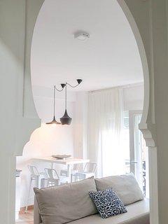 Entrada al salón con arco arabesco de Granada mezclado con estilo nórdico.