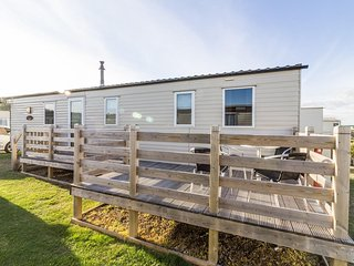 Ref 40078,  6 berth static caravan  with large decking by the  beach..